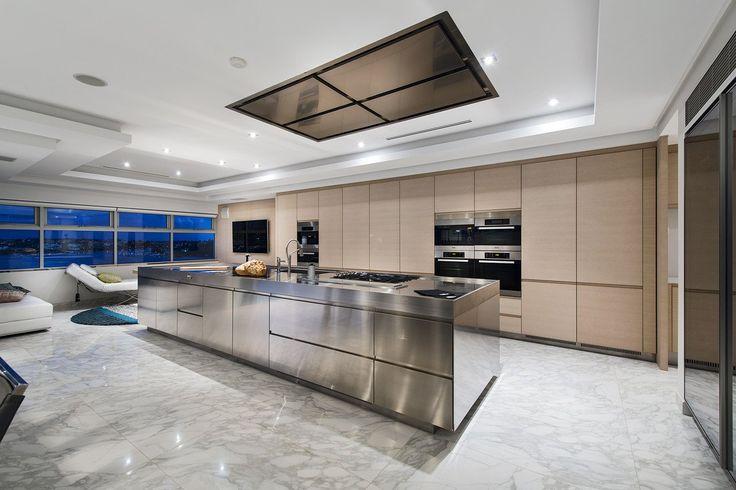 Idea cucina moderna maschile con mobili in legno chiaro, pavimenti in marmo e isola centrale in acciaio