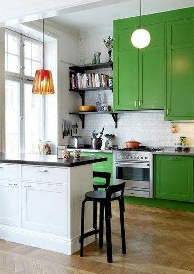 Cuina amb combinació d'armaris de color verd i petita península amb armaris blancs que fa funció de barra.