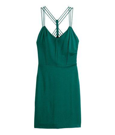 Een nauwsluitende jurk van tricot met decoratieve bandjes achter en een blinde ritssluiting aan de zijkant. Gevoerd met tricot.