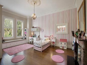 Children's room bedroom design idea with floorboards & sash windows using pink colours