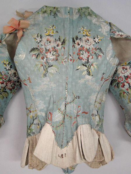 1751-1775 - France - Corps à baleines ouvert devant par un laçage, piqué fermé derrière dont les manches sabot trois-quarts sont démontables. Le corps est réalisé dans un taffetas bleu façonné et broché de fils de soie polychromes, motif placé de bouquets et rubans, animé d'une scène figurée, un jardinier arrosant un parterre de fleurs. Les manches sont maintenues au corps par des rubans de soie façonnée rose passé. L'ensemble est doublé dans une toile de coton ou de lin écrue.