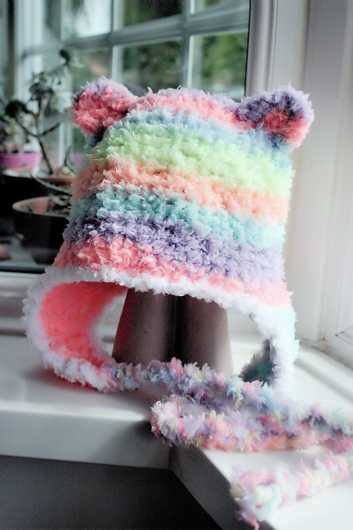 Crochet soft baby bear hat with ear flaps and tassles in light rainbow and white. Handmade with love by Babamoon   - Size 0 to 3m -   Shop now!  Click to learn more.  Can be made in other colours and sizes! #handmade #etsy