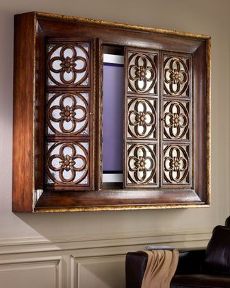 Need the perfect way to disguise your television?  The John-Richard Quatrefoil Wall Mounted Television Cabinet Bi-Folding Doors With Antique Mirrors Behind Gothic Quatrefoil Panels Set Within A Cavetto Mounded Frame.