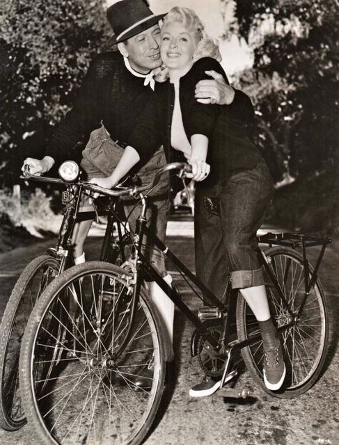 "Barry Sullivan, riding a bike with a ""B"" lamp bracket, goes cheek-to-cheek with Lana Turner. The couple were joined by Ezio Pinza and Marjorie Main in the 1951 MGM musical, Mr. Imperium."