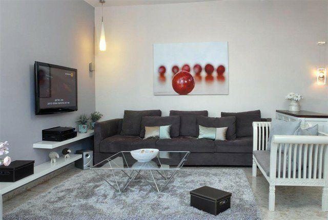 écran TV à fixation murale dans le salon avec canapé gris anthracite et tapis gris clair