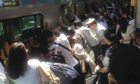 Train passengers and rail staff push a train car to rescue a trapped woman at Minami Urawa station.