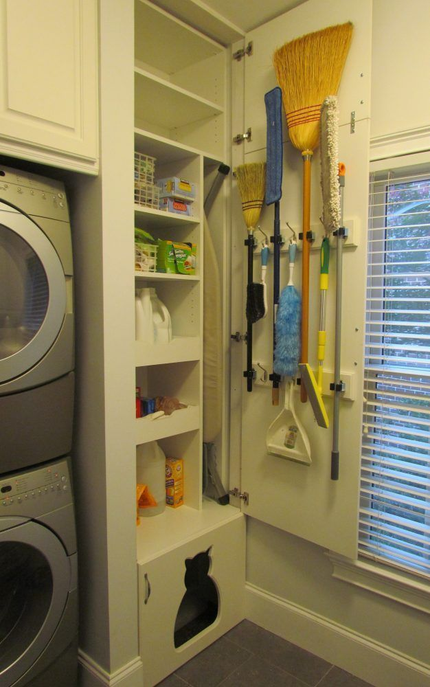 laundry room/pantry stacked washer dryer, brooms on cabinet door, pullout shelves, ironing board storage