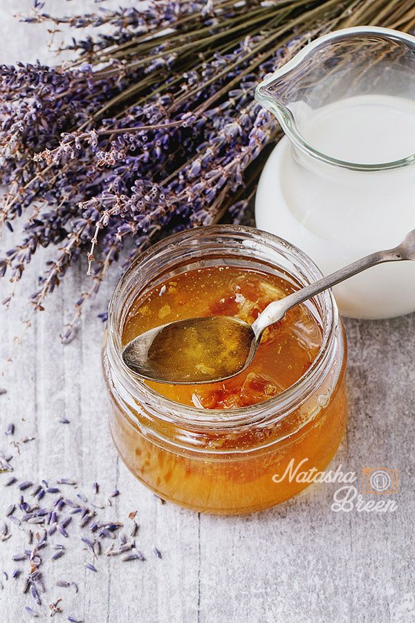 Honey, Milk and Lavender - Open glass jar of liquid honey with honeycomb and silver spoon inside, glass jug of milk and bunch of dry lavender over white wooden surface Rustic style.