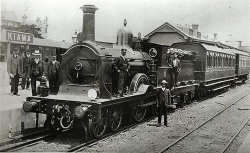 Kiama railway station. c1900. An early type locomotive with two early carriages.On the opposite side of the platform stand more recent corridor carriages used in those days for excursion trains.