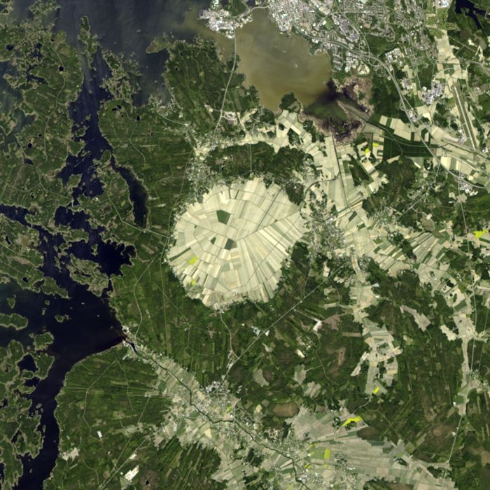 A false-colour image of Söderfjärden impact structure, made using Landsat 8 -satellite's Operational Land Imager bands 8, 3 and 1. Note the strikingly hexagonal plan view of the structure. The town of Vaasa is at the top of the image, and the diameter of the agricultural fields inside Söderfjärden is 5 km.