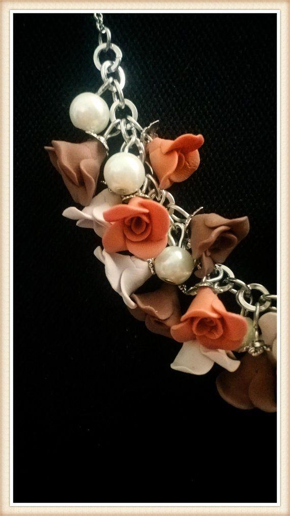 Collana con 19 piccole rose realizzate a mano in pasta polimerica ( Fimo ), arricchita da perle cerate. Lunghezza 47 cm. Le parti in metallo