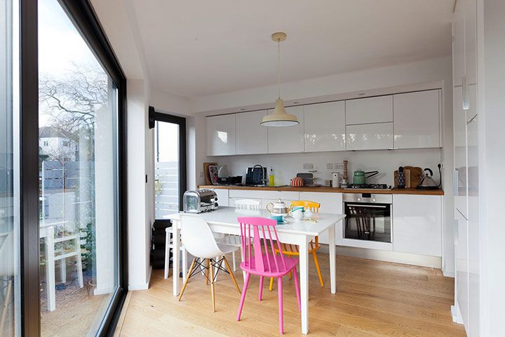 white cupboards, wood worktop, light, mismatched chairs