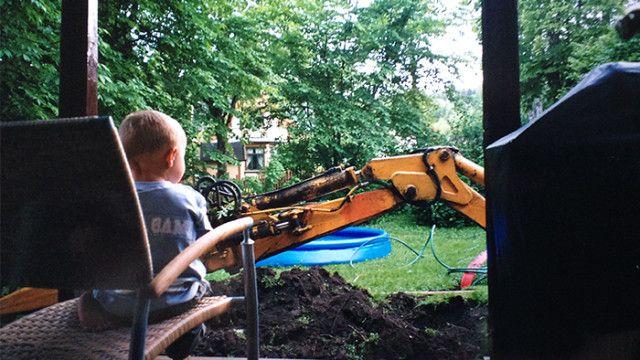 Liten gutt på veranda ser på gravemaskin