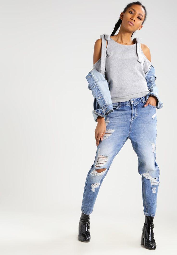 Boyfriend jeans + spalle nude + denim on denim. Le tendenze più glamour in un unico outfit