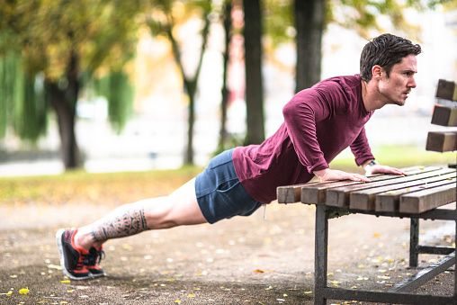 Fitness man doing push-ups at the outdoors park