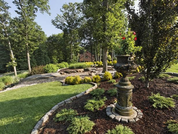 In this landscape bed designed by Cynthia Dodd, a stone pedestal plus container garden is a striking focal point. Cynthia says flea markets and antique shows are great places to shop for unique garden artwork.