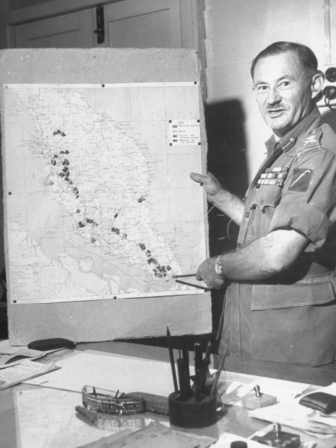 Major General Charles H. Boucher pointing out hot-spots on the map, Malaya, 1948