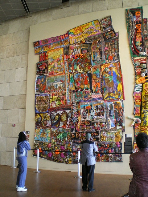 """A stunning public art commission at the Freedom Center is Aminah Robinson's amazing """"quilts"""" -- what she calls """"RagGonNons"""" because they """"rag on and on."""" They both tell a story of her family's journeys beginning -- in the upper left corner -- in Africa. The medium: cloth (including socks), thread, buttons, beads, ties, paper, paint, graphite, shells, and music boxes."""
