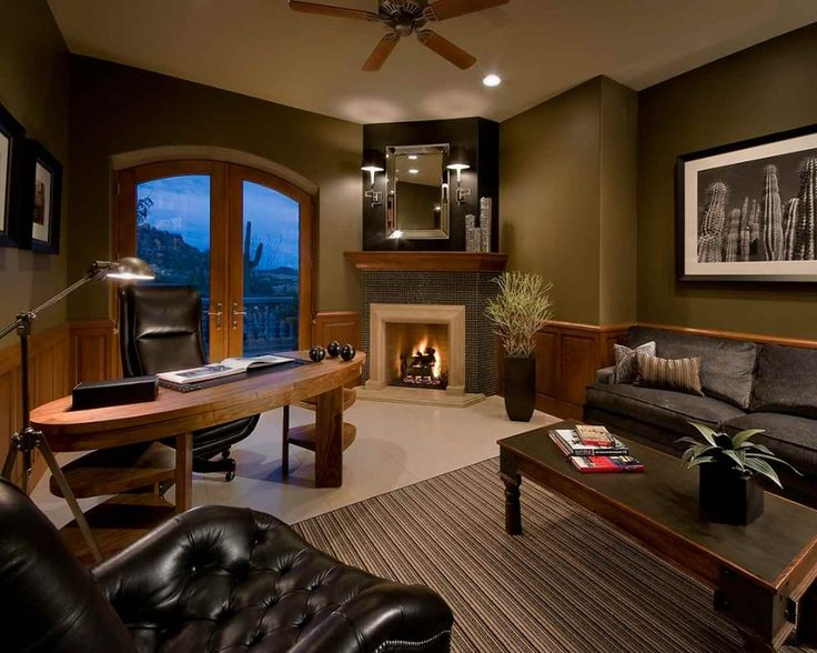 Large luxury home office and den with fireplace, wood desk and large sitting area with coffee table all done in dark color scheme