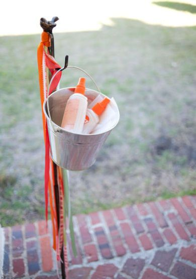 Use your plant shepard's hook to hang a bucket full of bug spray and suntan lotion for your guests... a little ribbon and you have a helpful, festive station!