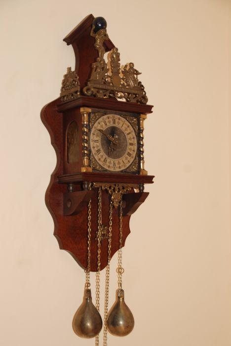"""Zaanse klok - FHS - ca. 1960  Mooie Zaanse klok gemaakt van wortelnoten hout. In goed werkende staat.Bovenop de kast staat een gegoten messing hekken met de tekst """"Nu elck syn sin"""" en daar bovenop is er een beeld van Atlas die de wereld draagt. De klok heeft twee zware koperen gewichten in peervorm. Onder de klok hangt een slinger van een man op paard. De klok is in goede staat met enkel wat ouderdomssporen. De klok is nagekeken. Elk half uur slaat de klok een tel en om het uur het hele…"""