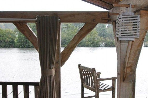 Mooie houten overkapping met speciale buiten gordijnen.