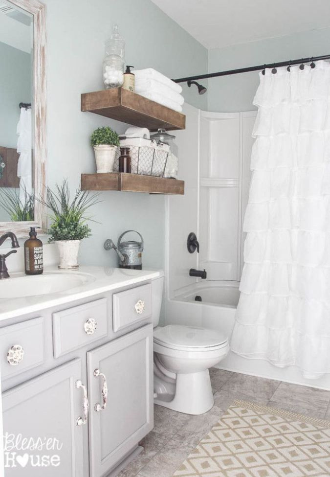 Sherwin Williams Sea Salt, shown in a bathroom with a lot of natural light has a higher LRV. Soft gray vanity looks beautiful in this farmhouse chic bathroom