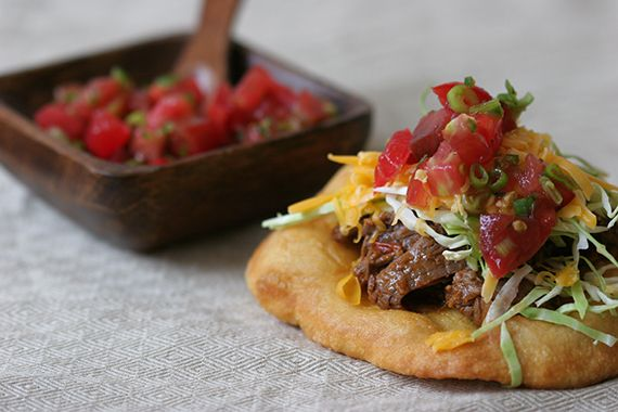 Fry Bread Tacos | By: Globetrotter Navajo fry bread tacos are typically made by topping fry bread with ground beef, shredded lettuce and cheddar cheese. In this recipe I've topped fry bread with Sonoran-style shredded beef, shredded cabbage, cheddar cheese and a simple tomato salsa, which is a little atypical but all components are prepared traditionally. | From: food52.com