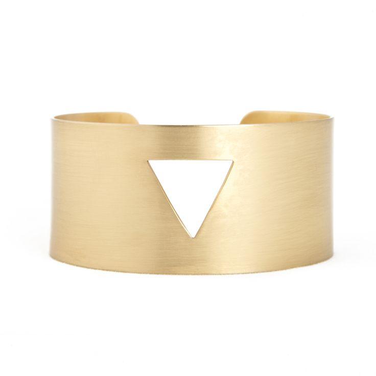 Pulsera con triángulo en el centro. Es rígida y autoajustable. Bañada en oro.