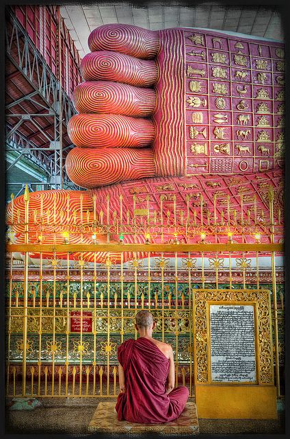 Monk meditating at the feet of the giant reclining Buddha in Chaukhtatgyi Temple in Yangon, Burma