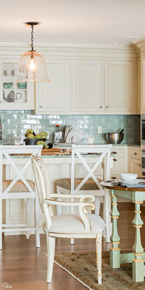 Lovely white kitchen. I really like the blue backsplash and the table! Look at those legs!