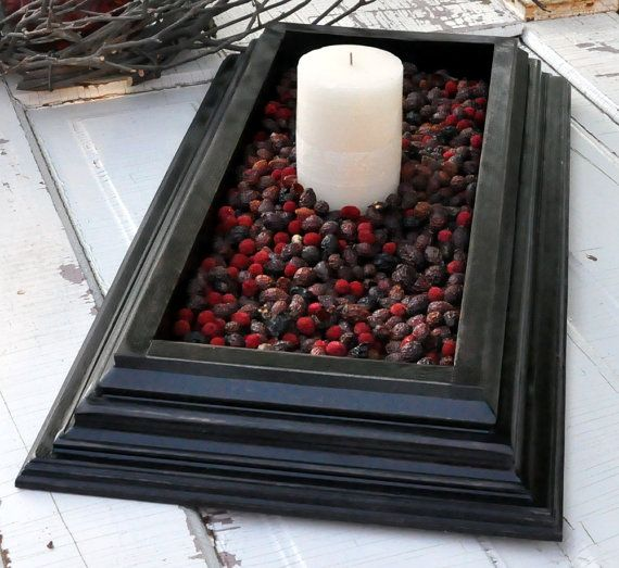 "If you have an old, deep frame laying around, here's a fun idea for you! Fill it with whatever filler is ""of the season,"" in this case, cranberries, (in the summer try sand, in the spring, dried green split peas, etc.) and add candles to create a fantastic center piece!"
