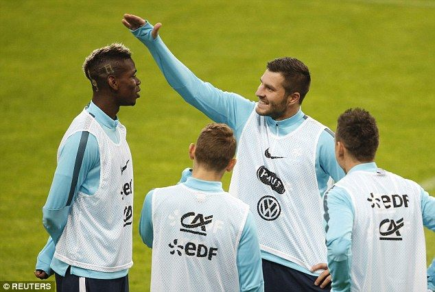 Pogba talks to France team-mate Andre Pierre Gignac (centre) in training in Saint-Denis on...
