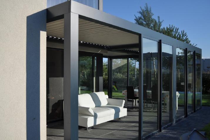 De terrasoverkapping van Biossun aangebouwd aan het huis als serre. Voordeel is dat je het binnen volledig droog houdt en dat je de warmte bij gure dagen behoorlijk goed vast kunt houden. Doordat de lamellen 176 graden kunnen draaien blijft bij warm weer de warmte echter niet hangen en bij erg warm weer kan de ruimte zelfs op natuurlijke wijze worden afgekoeld door de techniek van dit dak. De esthetische vormgeving maakt het helemaal af waardoor de traditionele serre definitief de aftocht…