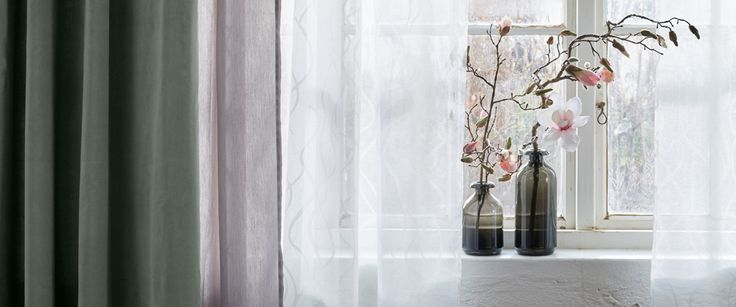 Close-up of sheer curtains in two layers and a thick curtain on top.