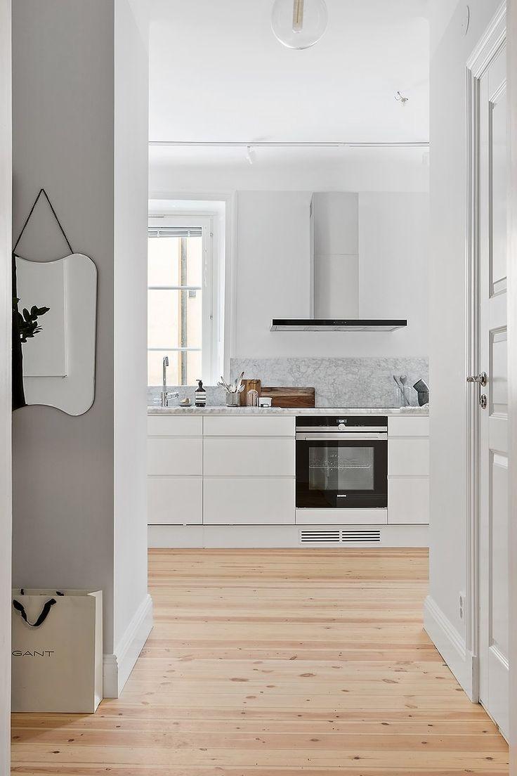 Köket är inrett med vita köksluckor, 80 cm djup bänkskiva av carrera marmor, nedsänkta eluttag i bänkskivan och nedfälld ho | Ballingslöv