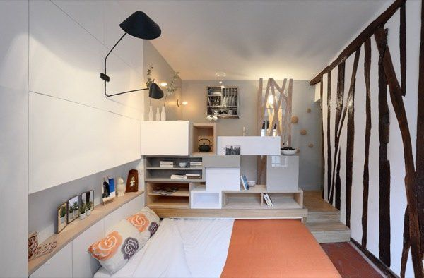 Woman Goes Tiny in a 129 Sq. Ft. Micro Apartment with kitchen, bed and bath.  The bed rolls right out of wall and if you roll it out only half way you can use it as a couch. This same multi-functional furniture unit is also the kitchen when you walk around the other side (directly above where the bed is hidden). http://tinyhousetalk.com/129-sf-paris-micro-apartment/