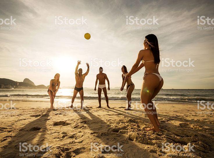 Grupo de jóvenes jugando voleibol de playa al atardecer. foto de stock libre de derechos