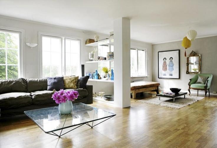 Stuen er romslig, og har lyse vegger og tak som er med på å skape en luftig følelse. Fra bærebjelken og inn mot vindusveggen er det laget åpne hyller fra gulv til tak, som fungerer som en fin romdeler. Hver side av stuen har også ulike stiler. Mens den ene siden er moderne med sitt glassbord og nye sofa, er den andre siden mer bohemsk med sitt lave bord, gamle stol og luksuriøse speil.