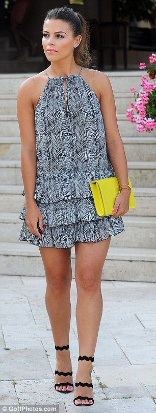 Bright as a button: Chloe Lewis wore a chic ruffled dress and carried a yellow clutch bag
