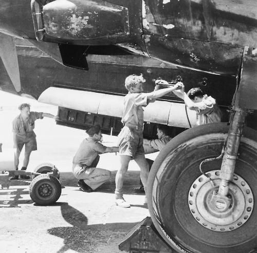 Armourers winching a 250-lb GP bomb into the bomb-bay of a Vickers Wellington at Shallufa, Egypt WWII