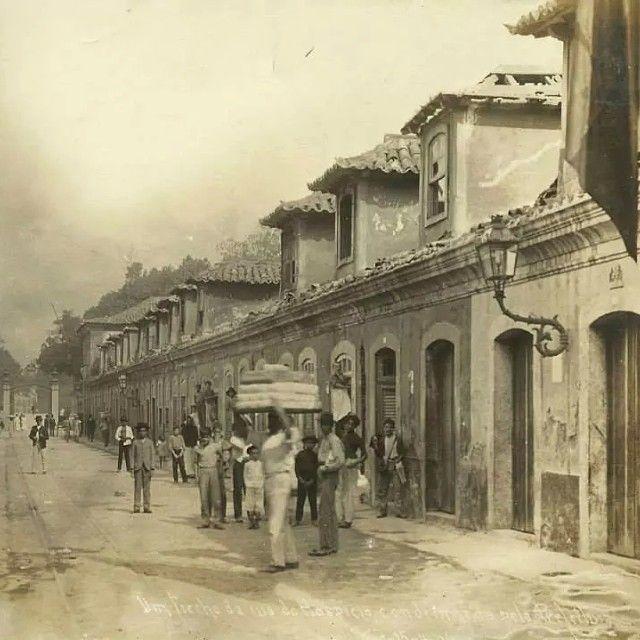 """A Rua Buenos Aires, em 1904, um pouco antes do """"bota-abaixo"""" do Prefeito Pereira Passos. Ao final da rua, à esquerda da foto, vemos uma das entradas do Campo de Santana. Essas belas construções coloniais, que já estavam com os dias contados, eram chamadas de """"cabeças-de-porco"""", cortiços onde a população pobre vivia amontoada em péssimas condições de higiene. De lá saíram para povoar as primeiras favelas da cidade."""