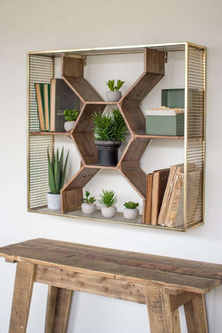 Sometimes nature is the best muse. Inspired by beehives, this honeycomb shelf is surrounded by antique brass. Plants and other oddities look lovely inside the wooden octagons. Artwork and notes clip n