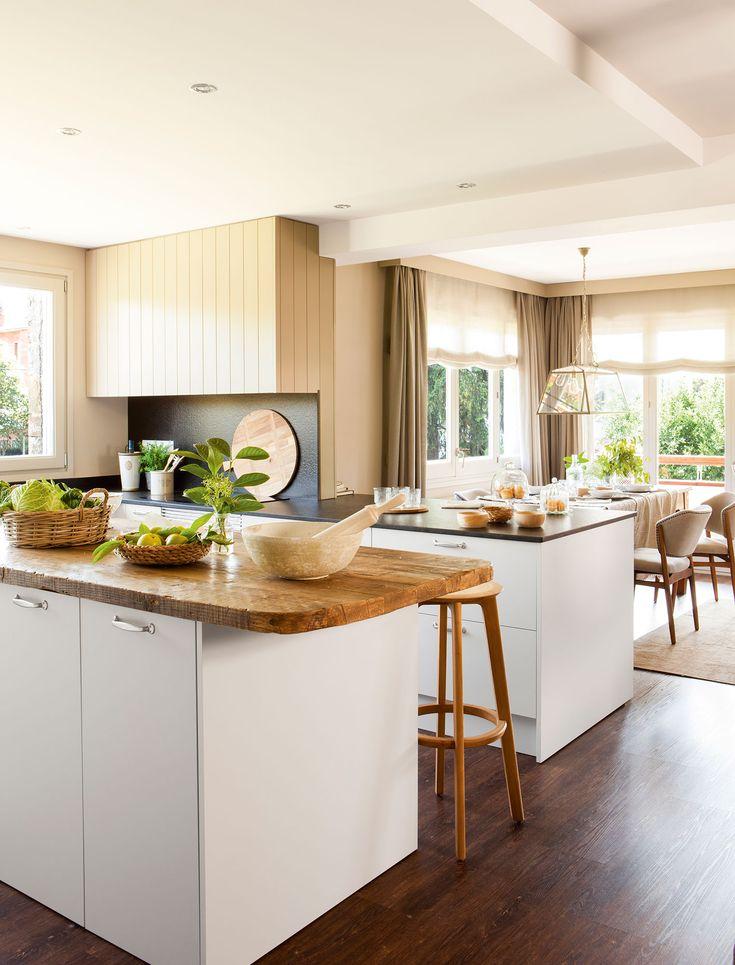 Cocina abierta al comedor con muebles en blanco y encimera de madera