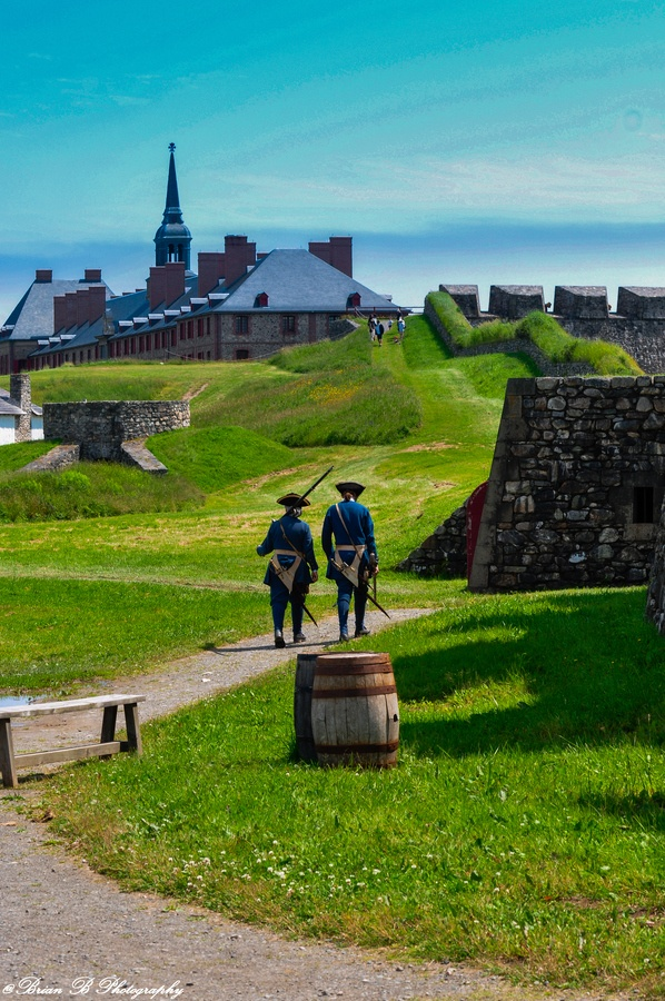 "Brian-B-Photography The Fortress of Louisbourg (French: Forteresse de Louisbourg) is a national historic site and the location of a one-quarter partial reconstruction of an 18th century French fortress at Louisbourg on Cape Breton Island, Nova Scotia. Its two sieges, especially that of 1758, were turning points in the Anglo-French imperial struggle for what today is Canada. Two ""Soldiers"" travel from the main gate area towards the Citadel"