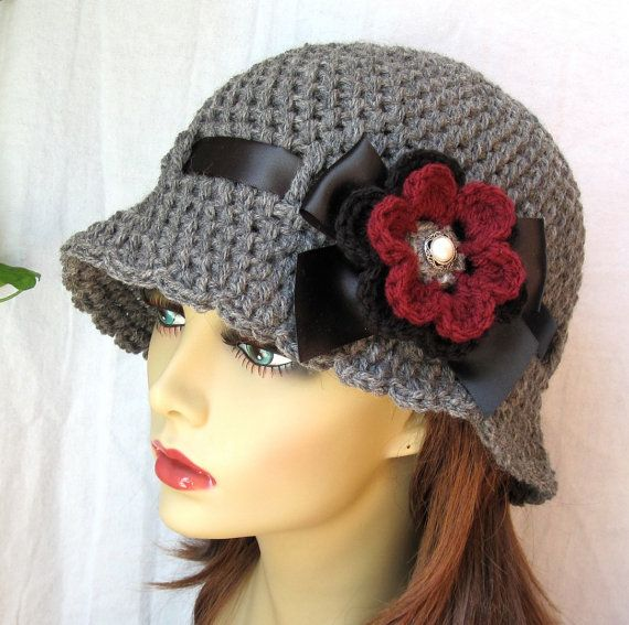 Chic Crochet Women's Hat in Gray (shown). Cloche Hat. Handmade soft Acrylic or Wool Blend yarn, depending on availability. Embellished with black ribbon tied into a bow and a gorgeous removable flower pin. Hat can be worn with or without flower pin. Flower pin can be worn with other wardrobe (sweaters, jackets, dress, scarves, etc.). The bow is secured and cannot be undone. The ends of ribbon are treated so they will not fray easily. If youd like the flower to be permanently attached…