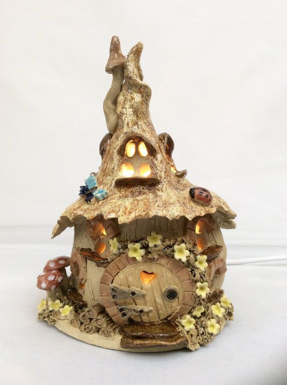 I made this fairy house electric lamp from stoneware clay and glazes then fired it in an electric kiln to 1,220 degrees centigrade. It is made entirely by hand without the use of a mould so each one is totally unique. I cut out the windows and door so the light shines through to create a lovely warm glow. It is fitted with a 3 pin plug and a small Pygmy bulb and is CE marked. Measurements. Approximately 25 cm tall, 16 cm wide and 16 cm deep. This item will be delivered by a courier service…