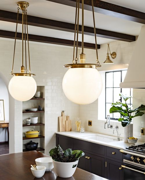 Old World Brass Globe Pendants And Black Kitchen Cabinets With Brass Hardware