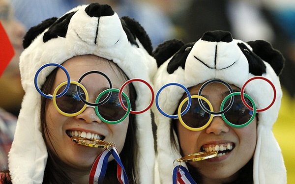 Two Chinese fans pause for photos prior to the Women's Synchronized 10 Metre Platform Diving final at the Aquatics Centre. (AP Photo/Jae C. Hong)