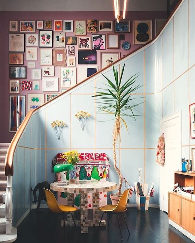 Although we can't see the entire #wallgrouping from this angle, we're pretty confident it's a phenomenal arrangement! The large grid houses TONS of #artwork in a variety of sizes and styles. But, what we love almost as much as the #customframedart itself is the gold grid pattern on the cool blue stair wall. The #geometric rectangular boxes mimic the feel of the oversize wall grouping. Just spectacular and certainly inspirational!! #CustomFraming #LarsonJuhl #InteriorDesign